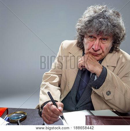 The senior man in cloak as detective or mafia boss writing in a notebook with pen at table. Studio shot on gray in retro stile poster