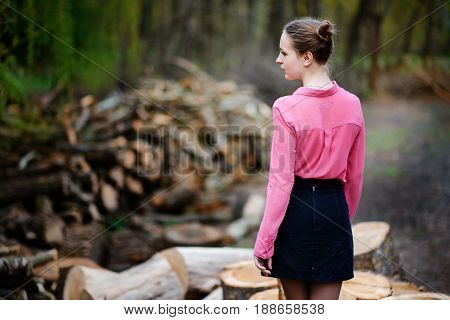 Beautiful Young Woman Standing Back To Camera On Stack Of Felled Tree Trunks In The Forest