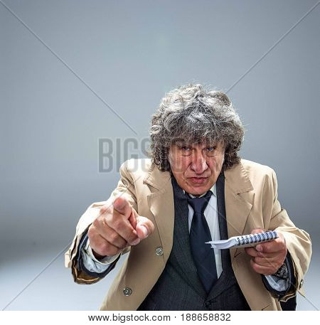 The senior man in cloak as detective or mafia boss pointing at camera at table. Studio shot on gray in retro stile