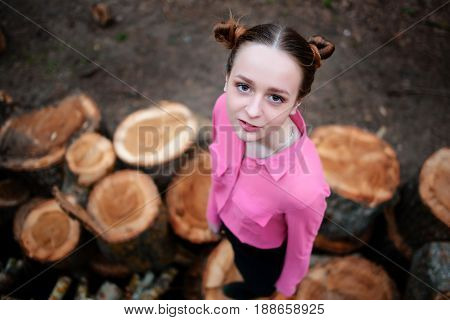 Beautiful Young Woman Standing And Looking At The Camera On Stack Of Felled Tree Trunks In The Fores