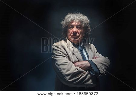 The senior man in cloak standing as detective or mafia boss. Studio shot on gray in retro stile in the light and smoke ray