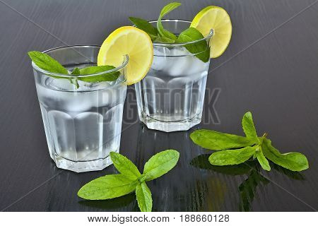 Fresh mint. Water in glass. Lemon and mint. Refreshing drink. Detoxification cure. Fresh water and forest mint. Chilled water flavored with lemon and mint.