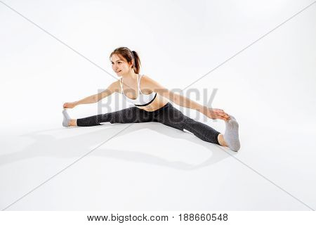 Young athlete sits on twine at empty white background