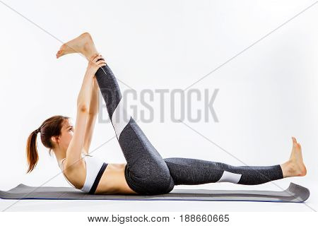 Sporting girl engaged in fitness on gray rug at isolated background