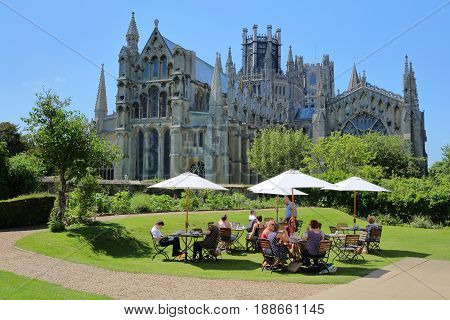 ELY, UK - MAY 26, 2017: People enjoying a sunny day at the terrace of a restaurant with a magnificent view of the Cathedral from the East