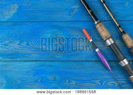 Fishing tackle - fishing rod fishing float on beautiful blue wooden background