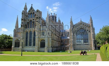 ELY, UK - MAY 26, 2017: View of The East part of the Cathedral from a public garden with people enjoying a sunny day