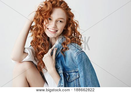 Young sincere girl with red curly hair and freckles smiling looking in side over white background. Copy space.