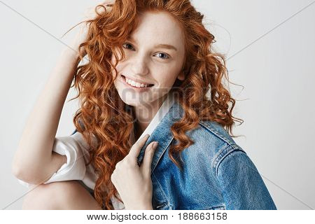 Happy cheerful foxy girl in jean jacket smiling looking at camera posing over white background.
