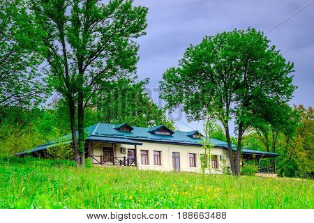 Cottage under the cloudy sky a beautiful place to relax around nature green grass and trees