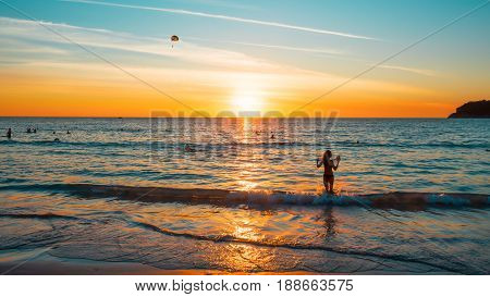 Sunset on a tropical beach. The picture aspect ratio is 16:9. The face and figure of the girl are changed