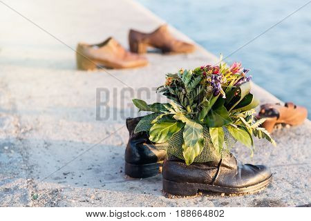 Shoes on Danube with bunch of flowers. Holocaust Memorial in Budapest Hungary.