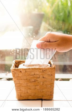 Male hand pulling the white facial tissue from a box. Brown rattan weave. (soft focus)