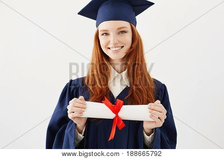 Happy foxy girl graduate in cap smiling looking at camera holding diploma. White background.