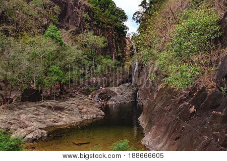Koh Chang, Thailand - December 20, 2015: Realistic image of lots of tourists in the Khlong Phlu Waterfall, Mu Koh Chang National Park. Unidentified people admiring the waterfall swim and take photos.