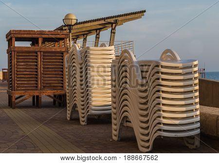Vacation beach concept. Sunbeds and empty beach cabin on the beach near the sea.