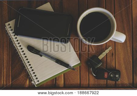 Cup Of Coffee, Cell Phone, Note Pad, Pencil And Keys On A Wood Table