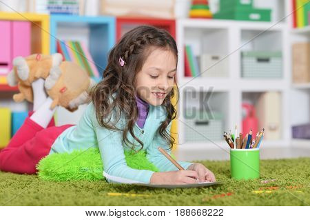 Little girl lying on floor and drawing picture