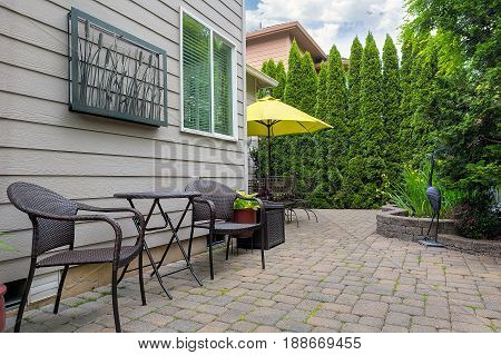Bistro chairs and table on stone paver bricks patio in garden backyard with pond