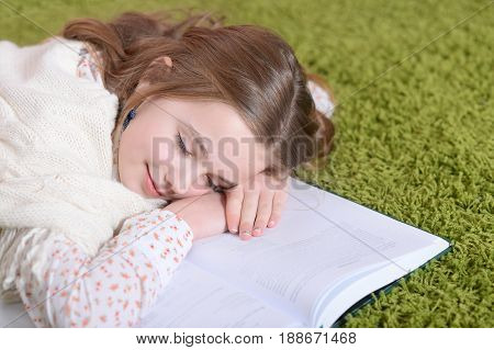 Portrait of a cute little girl lying on green carpet