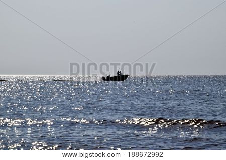 The Boat Rushes By The Sea. In The Boat People. Seascape In The Evening. Silhouette Of A Motor Boat