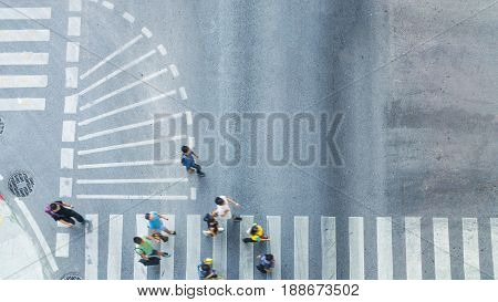 Busy city people crowd move to pedestrian crossing on traffic road (Aerial photo top view)