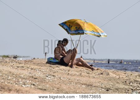 Two Gay Men On The Beach Under An Umbrella. Homosexual Couple On The Beach.