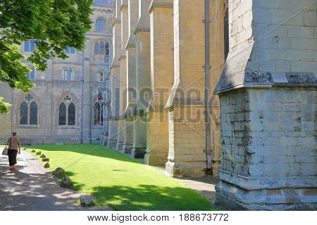 ELY, UK - MAY 26, 2017: View of the south part of the Cathedral on a sunny day with an elderly woman walking on the left side