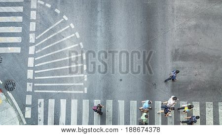 Busy city crowd move to pedestrian crossing on traffric road (Aerial photo top view)