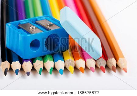 eraserc and sharpener on colored pencils. white background