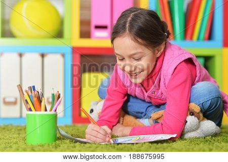 Cute little girl lying on floor and drawing picture