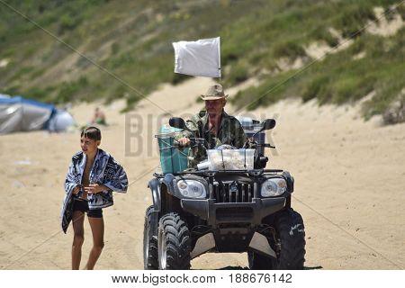 A Man Is Riding A Quad Bike Along The Sandy Beach Of The Sea.