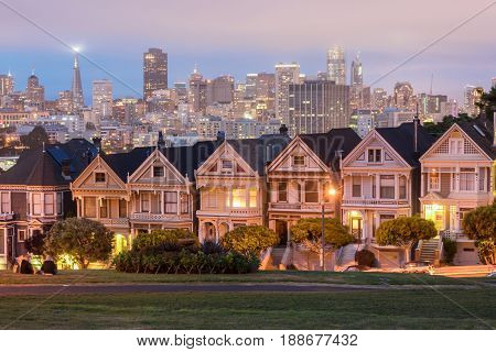 Dusk Over The Painted Ladies. Iconic Victorian Houses and San Francisco Skyline in Alamo Square, San Francisco, California, USA.