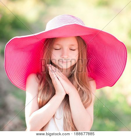 Cute blonde girl 4-5 year old with closed eyes wearing big hat outdoors. Summer time.