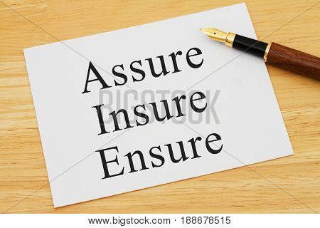 Learning to use proper grammar A white card on a desk with a pen with words Assure Insure and Ensure