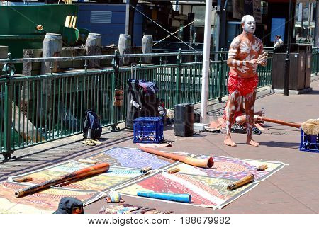 SYDNEY AUSTRALIA - OCTOBER 11 2015: Aboriginal male street busker is giving performance with musical instruments laid out nearby on the ground by the pier at Circular Quay.