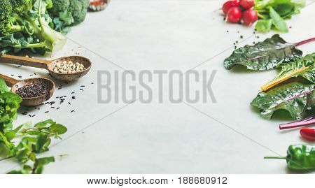 Fresh raw greens, vegetables and grains over light grey marble kitchen countertop, copy space. Clean eating, healthy, vegan, vegetarian, detox, dieting food concept
