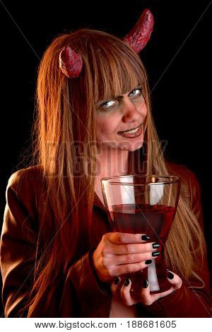 Devil girl in red light with a jug of blood in her hands