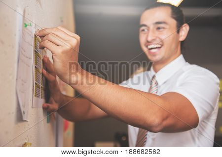 Focus on hand. Happines of Businessman smiling and preparing documents on wall for meeting in office.