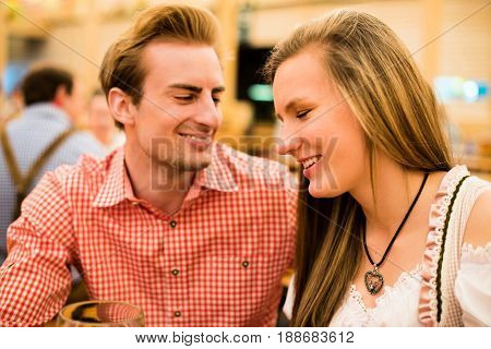 Young couple in traditional Bavarian Tracht - Dirndl and Lederhosen - in a beer tent at the Oktoberfest enjoying their beers and flirting with each other