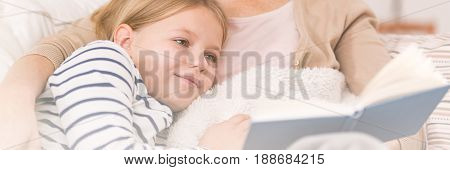 Girl reading a book with her mother
