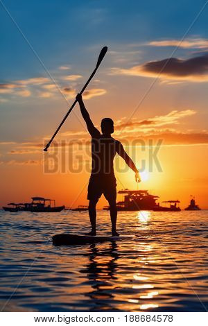 Paddle boarder. Black sunset silhouette of young sportsman paddling on stand up paddleboard. Healthy lifestyle. Water sport SUP surfing tour in adventure camp on active family summer beach vacation.