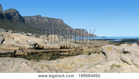 FROM CAPE TOWN SOUTH AFRICA, CAMPS BAY, WITH HUGE BOULDERS IN FORE GROUND AND A MOUNTAIN IN THE BACK GROUND
