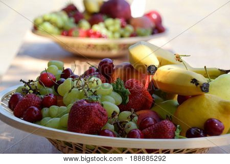 Close view on the fruit baskets in the shade. Full of different fruits...banana, strawberries, grape, cherry...