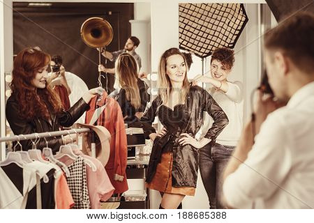 Stylist putting stylish clothes on fashion model at backstage