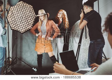 Stylist and professional model during photoshoot backstage