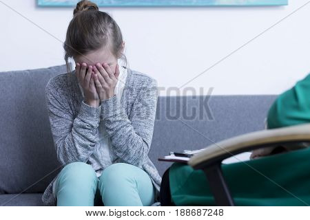 Sad teenage girl crying during psychological session with therapist
