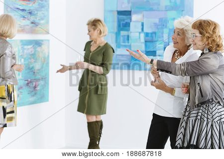 Two female friends admiring the painting in art gallery