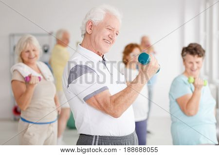Older man exercising biceps using dumbbell during fitness classes