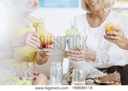 Elegant senior women drinking cocktails in art gallery after exhibition